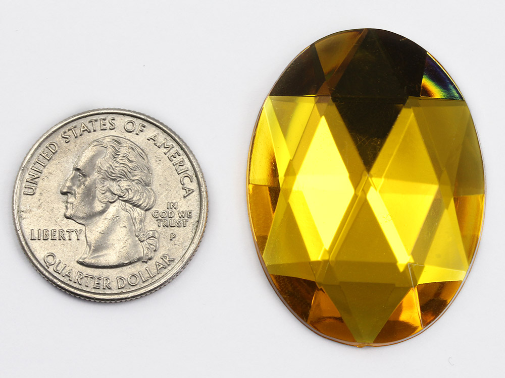 large gold topaz flat back gem next to a quarter